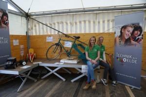 """Merle Teckentrup und Sarah Peter betreuten den Wettbewerb """"Technik aus Oelde"""". Das Wettermobil ist ganz links, daneben das Müllaufsammlungsgerät und dem Rasenbelüftungsfitnessgerät"""